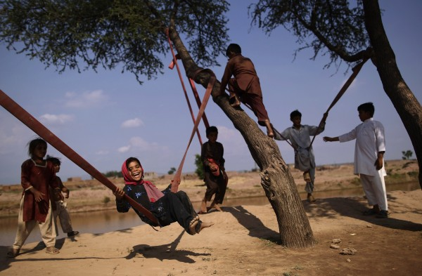 Pakistani Dawlat Gul, 7, (third left) enjoys playing on a swing along with other children on the outskirts of Islamabad, Pakistan on Friday, July 13, 2012.