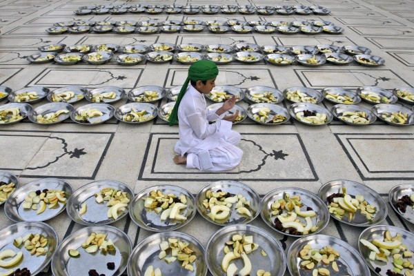 A Pakistani boy prays next to plates of fruits donated to worshippers to break their fast, on the first day of the holy fasting month of Ramadan, in a mosque in Karachi, Pakistan, Saturday, July 21, 2012. During Ramadan, the holiest month in Islamic calendar, Muslims refrain from eating, drinking, smoking and sex from dawn to dusk.