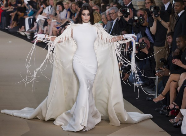 Actress Fan Bingbing wears a creation by French designer Stephane Rolland, as Kanye West (right) watches Rolland's presentation of his Women's Fall Winter 2013 haute couture fashion collection, in Paris, France, Tuesday, July 3, 2012.