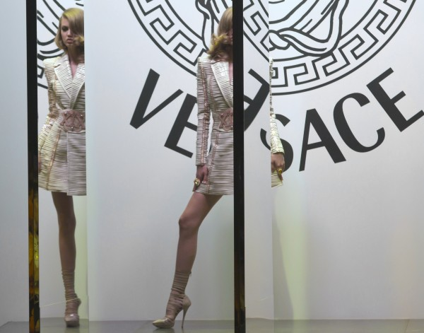 A model stands behind a set of mirrors as she wears a creation by fashion designer Donatella Versace during her Women's Fall Winter 2013 haute couture fashion collection, for fashion house in Paris, France on Sunday, July 1, 2012.