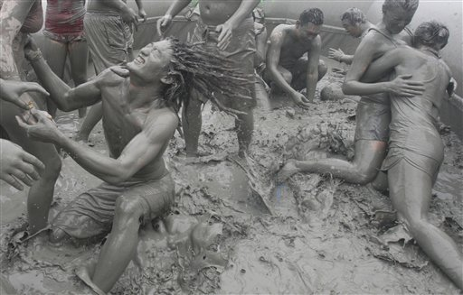 Tourists play with the mud during the 15th annual mud festival on Daecheon Beach in Boryeong, South Korea on Sunday, July 15, 2012. The festival features mud wrestling, mud sliding and mud king contest.