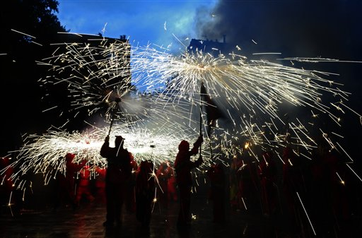 Revelers hold torches as they take part in 'Correfoc' (Run with fire) party in Barcelona, Spain on Sunday, July 15, 2012. Correfocs or &quotfire-runs&quot are among the most striking features present in Catalan festivals. In the correfoc, a group of individuals will dress as devils and light fireworks. While dancing to the drums of a traditional gralla, they will set off their fireworks among crowds of spectators.