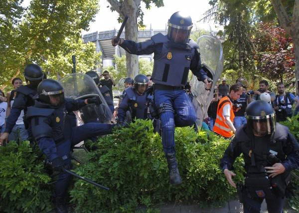 Police riots run after the demonstrators during the coal miners' march to the Minister of Industry building in Madrid on Wednesday, July 11, 2012. Coal miners angered by huge cuts in subsidies converged on Madrid for protest rallies after walking nearly three weeks under a blazing sun from the pits where they eke out a living.