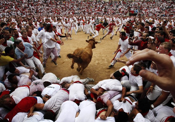 A cow jumps over revelers in a bullring during the second running of the bulls at the San Fermin fiestas, in Pamplona northern Spain on Sunday, July 8, 2012.