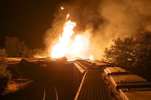 Flames rise from a derailed freight train early Wednesday, July 11, 2012 in Columbus, Ohio. Part of a freight train derailed and caught fire in Ohio's capital city early Wednesday, shooting flames skyward into the darkness and prompting the evacuation of a mile-wide area as firefighters and hazardous materials crews worked to determine what was burning and contain the blaze.