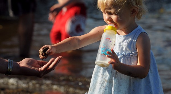 Twenty-two-month-old Noelle Comstock hands her father, John, a handful of wet beach sand while playing in the water of Pushaw Lake at Gould's Landing in Orono Sunday.