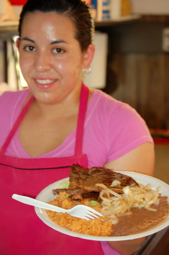 Juana Vazquez, 21, will be busy for the next few weeks, serving up ethnic breakfasts, lunches and dinners for blueberry harvest rakers living within the Jasper Wyman migrant housing complex in Deblois. This steak plate is among the best-selling entrees served by her family's mobile kitchen.