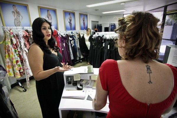 Alicia Estrada (left) founder of the clothing company Stop Staring, talks with online coordinator Diane Gonzalez in the showroom of the Paramount, Calif., enterprise.