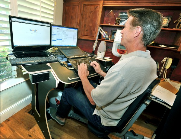 Bryan Wassom, a high-tech salesman, sits at his combination desk-and-bike at his home in Pleasanton, California, Friday, July 6, 2012. Wassom and his son Alex Wassom developed the ActivOffice Exercise Desk for people who work at a desk and don't get enough exercise.
