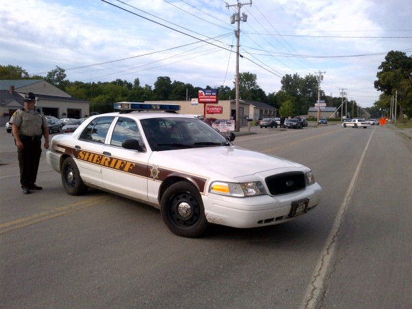 Penobscot County Sheriff's Office deputy Mark Lloyd blocks the Main Road in Hampden on Friday where witnesses say a standoff is underway.