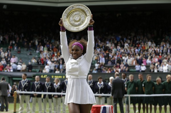 Serena Williams of the United States shows off the championship trophy after beating Agnieszka Radwanska of Poland during the women's final match at the All England Lawn Tennis Championships at Wimbledon, England, Saturday, July 7, 2012.