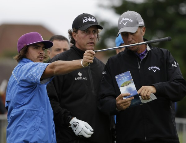 Rickie Fowler of the United States (left) and Phil Mickelson of the United States, (center) gesture during a practice round at Royal Lytham & St Annes golf club ahead of the British Open Golf Championship, Lytham St Annes, England Tuesday, July  17, 2012. Man at right is unidentified.