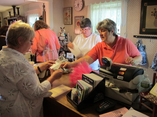 Carol Metthe, owner of Bittersweet Gift Shop in Bucksport (right) hands a customer a receipt during the town's first Cash Mob on Friday, July 27, 2012.