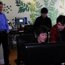 Charlie White of CashStar shows Sen. Susan Collins a project to incorporate digital gift-giving into a social media setting on Jan. 12, 2012, as CEO David Stone, left, looks on. Behind Collins and White is a videographer taping the visit for the company