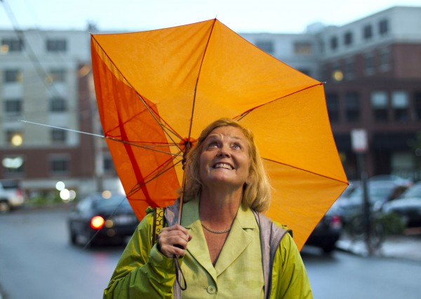 U.S. Rep. Chellie Pingree, D-Maine, looks up to the skies during a thunderstorm that damaged her umbrella and forced the postponement of the Fourth of July fireworks show in Portland.