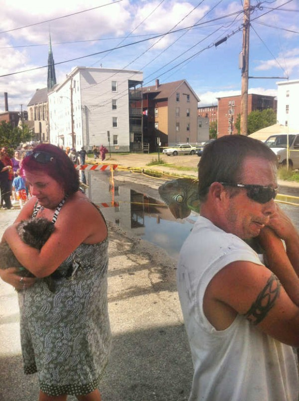 Tracy Benoit (left) is overcome with joy as she cradles her cat, Max, who was found in the remains of an apartment building fire on River Street on Tuesday afternoon. Her boyfriend, Scott Galarneau (right), tearfully holds their pet iguana, Iggy, who also was found in their first-floor apartment along with a snake, a tarantula and a dog.