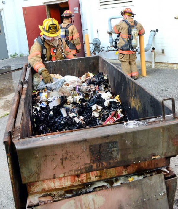 A Lewiston firefighter examines the Dumpster that caught on fire at Blake Street Towers in Lewiston Monday evening.
