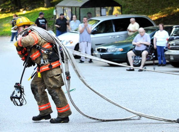A Lewiton firefighter drags hose into Blake Street Towers during Monday's fire.