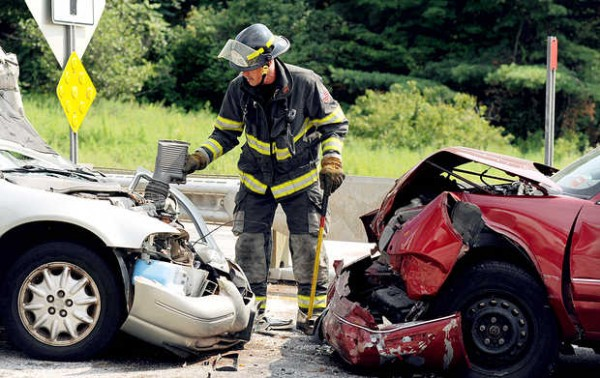 Capt. Chip Keene of the Auburn Fire Department cleans up the scene of a two-car accident on the Veterans Memorial Bridge in Auburn on Tuesday.