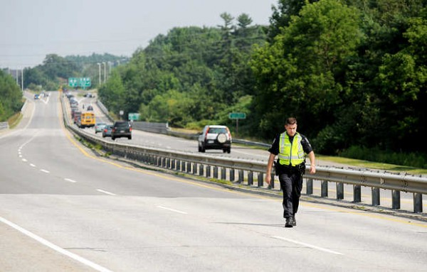 Barry Schmieks of the Auburn Police Department walks along the westbound lane of the Veterans Memorial Bridge on Tuesday.