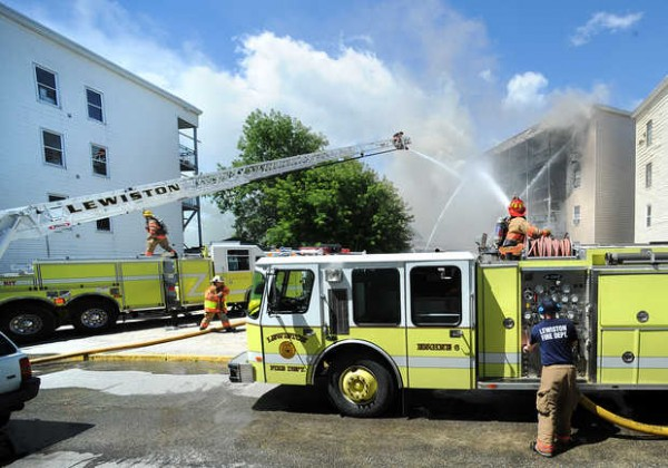Firefighters battle a fire on River Street in Lewiston Tuesday morning.