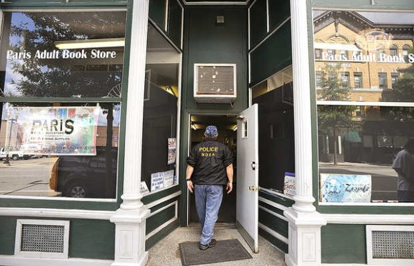 A drug agent walks into the Paris Adult Book Store on Lisbon Street in Lewiston on Thursday.