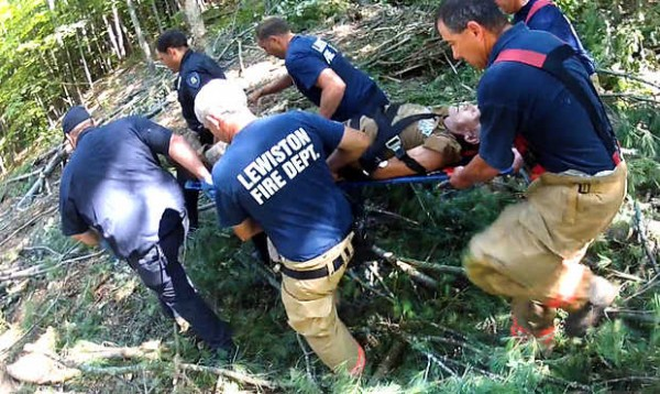 United Ambulance personnel and Lewiston police and firefighters carry a logger through the woods off River Road in Lewiston on Wednesday morning, July 11, 2012 after he was pinned beneath his skidder.