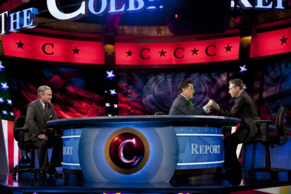 Stephen Colbert, center, and Jon Stewart, right, hold hands during The Colbert Report, as Trevor Potter looks on Thursday, Jan. 12, 2012, in New York. During the episode, Colbert legally transferred his super political action committee to Stewart, his friend and Comedy Central cohort.