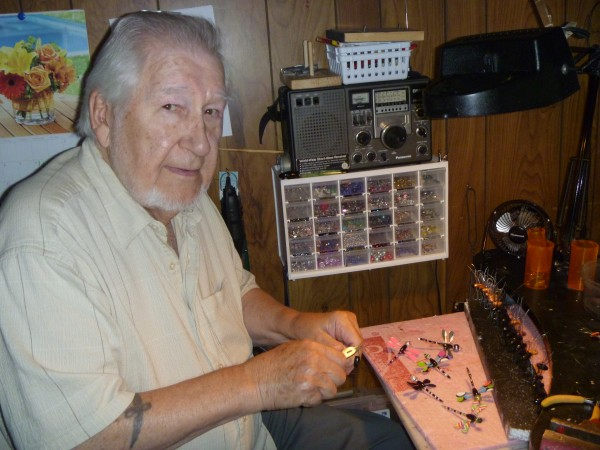 Larry Payeur of Bangor works on the dragonfly pins he makes to raise funds for charity.