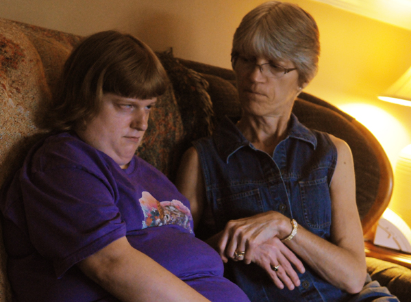Rita Spencer (right) sits on the couch with her daughter, Katie, at the family's Hermon home in June 2012. Katie suffers from multiple physical ailments including blindness and can lose consciousness without warning. Katie has been denied housing and care in a group home because DHHS says she does not fit the criteria.