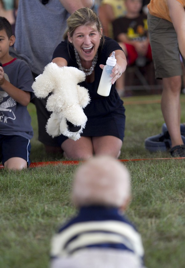 Angela Morris of Cumberland uses a stuffed animal and a milk bottle to encourage her baby, Jameson Brainerd, age 10 months, toward the finish line in the Diaper Derby on Sunday at the Yarmouth Clam Festival.