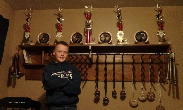 Sam Chapman poses with his trophies earned by winning 1st, 2nd or 3rd place at Taekwondo Tournaments.  The shelf was custom-made by his father, Chris Chapman.