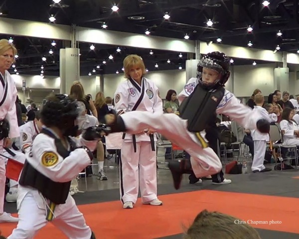Sam Chapman executing his flying move, a 3-point jump kick to his opponent's head during a Taekwondo Tournament.  Safety gear is required and competitors must spar with respect.  Excessive force is forbidden and cause for disqualification.