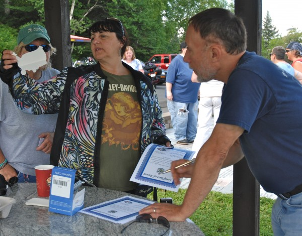 Women of the Road North Shore, Massachusetts chapter director Sue Fountain (center) checks out some souvenirs during her group's recent stop-over at the Four Corners Tour Park in Madawaska as park representative Joe LaChance, prepares certificates of welcome for each visitor.