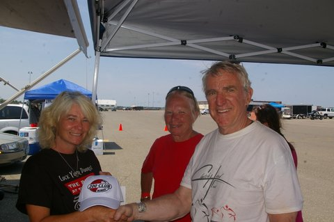 Bangor's Dave Sleeper went 200.540 mph at the Loring Speed Trials Land Speed Races and set a record in his class, making him eligible for the Loring Timing Association's 200 mph club. Theresa Brown of LTA recognizes Sleeper with a club commemorative cap while Sleeper's wife Anne looks on.