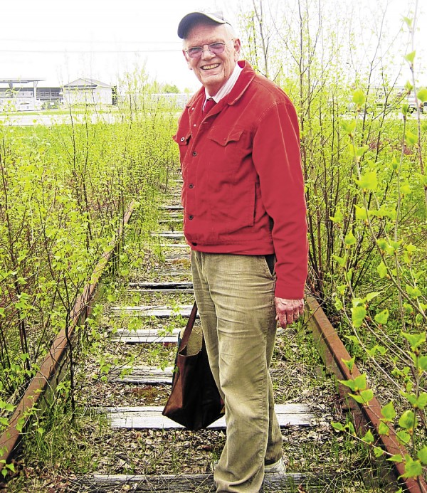 Dr. David Bergquist, a Hermon historian, stands on an abandoned section of railroad track that once extended to Dow Air Force Base from a siding off the Odlin Road. Behind Bergquist are Outer Hammond Street and the Hammond Lumber Co. store.