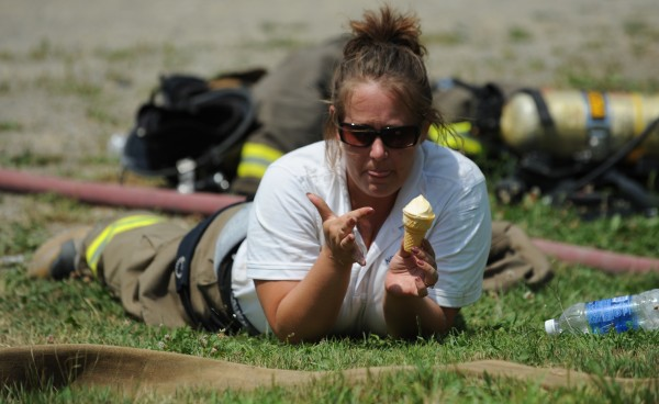 Newport fire fighter Amanda Chretien enjoys ice cream as her crew rests while fighting a structure fire at 289 West Etna Road in Etna on Monday, July 23, 2012, in mid-80-degree heat.