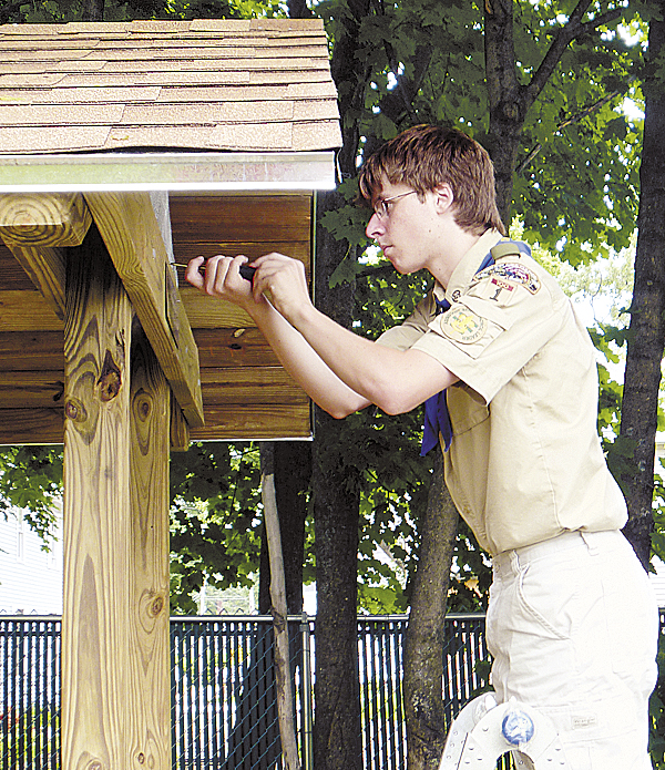 Brewer Boy Scout Mason Duplissie makes final adjustments to the picnic table and shelter recently built for the Brewer Public Library. Duplissie conceived and organized the project as part of the requirements for him to become an Eagle Scout.