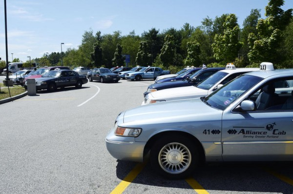Taxis wait in a holding lot at the Portland International Jetport for their chance to queue outside the terminal. Renewed debate over the number taxis working the airport has spurred debate about whether the the city should limit the number of cabs across the city.