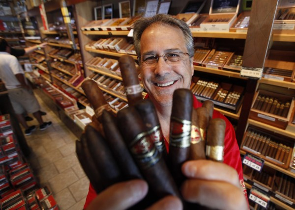 The owner of Havana Connections cigar shop, George &quotShorty&quot Koebel, holds a bunch of cigars at his store in Richmond, Va., Wednesday, June 20, 2012.  The Food and Drug Administration intends to regulate cigars under a 2009 law that gave it authority over the tobacco industry and cigar makers and aficionados are pushing to ensure their livelihoods and the products they enjoy. (AP Photo/Steve Helber)