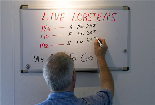 Bob Coppersmith updates the price board at Dock's Seafood Restaurant in South Portland dropping the price of five small lobsters down to $24 on Thursday, June 28, 2012. Many stores are selling the king of seafood for under $5 a pound, making it cheaper than bologna by weight.