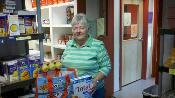 Falmouth Food Pantry manager Jill Fox packs groceries into one of the pantry's &quotKids' Bags&quot for needy families with children. The pantry, which operates in donated space at Town Hall, 271 Falmouth Road, is open approximately six times a month.