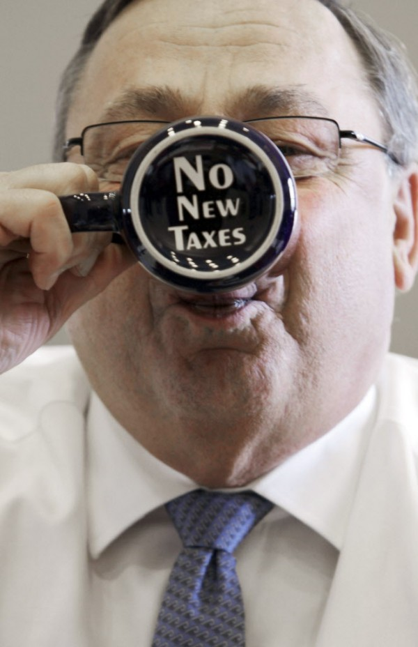 Gov. Paul LePage takes a sip out of a coffee mug displaying a &quotno new taxes&quot message on the bottom during an April press conference at his office at the State House in Augusta, Maine.