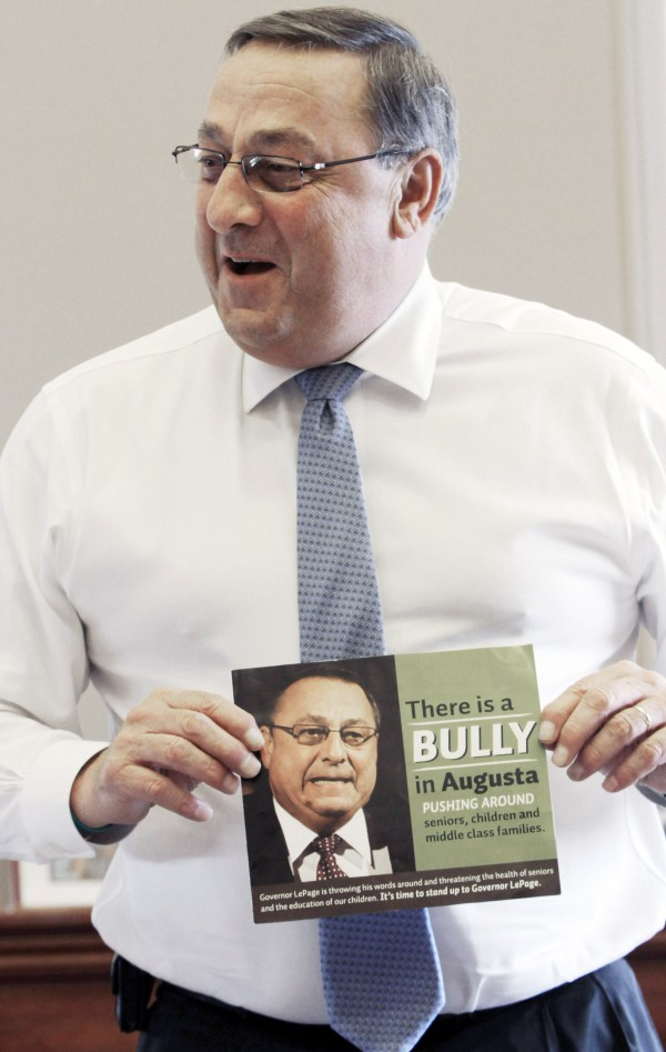 Gov. Paul LePage talks about his sense of humor while holding a poster that reads &quotThere is a bully in Augusta pushing around seniors, children and middle class families,&quot during an interview with The Associated Press at his office at the State House in Augusta, Maine, on Friday, April 27, 2012.