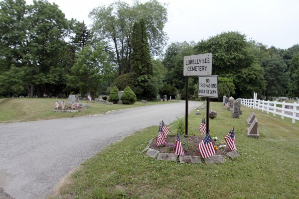 This June 29, 2012 photo shows the entrance to the cemetery in Lowellville, Ohio. Trustees there received a proposal earlier this year to lease cemetery mineral rights for $140,000 plus a percentage of any royalties for any oil and gas, raising a tricky question: Are cemeteries a proper place for drilling? (AP Photo/The Vindicator, Robert K. Yosay)