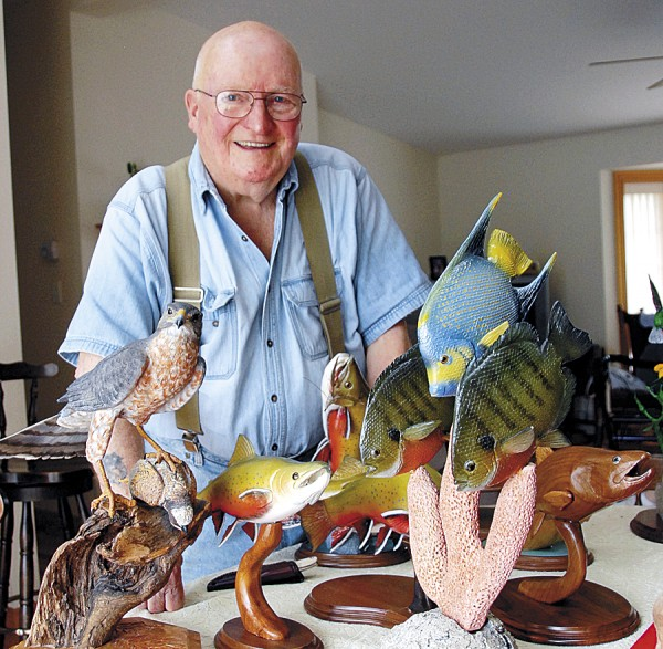 George Snedden, an 85-year-old wood carver who lives in Old Town, displays several exquisite carvings that he has done. Among the wildlife he has captured in wood are (from left) a full-size Cooper's hawk that has caught a quail; trout; and other fish. Snedden took up wood carving after retiring in 1991.