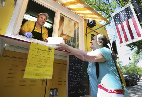 Christophe Ensenat hands Anna Withers dessert crepes to go, at Christophe's Crepes truck in downtown Fairfield, Conn., in June 2012. After four months of work by a Portland, Maine task force and a round of review and recommendations by the planning board, a slate of ordinance changes pertaining to the food trucks was given first reading by the Portland City Council on Monday, July 2, 2012.