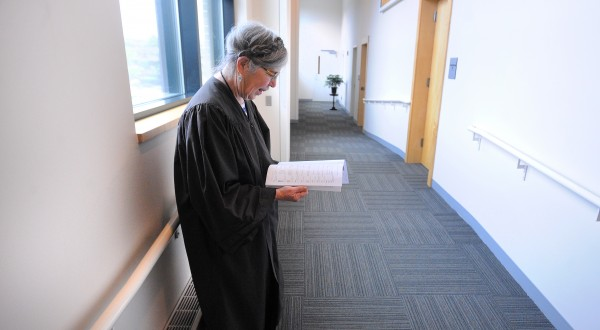 District Court Judge Jessie Gunther looks over the list of cases for the day, before entering the courtroom at the Penobscot Judical Center in Bangor. Judge Gunther retired at the end of June after nearly 32 years on the bench.