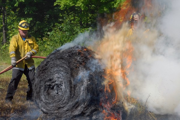 Firefighters  work to extinguish a hay field fire off Bagley Mountain Road in Lincoln on Wednesday, July 11, 2012.