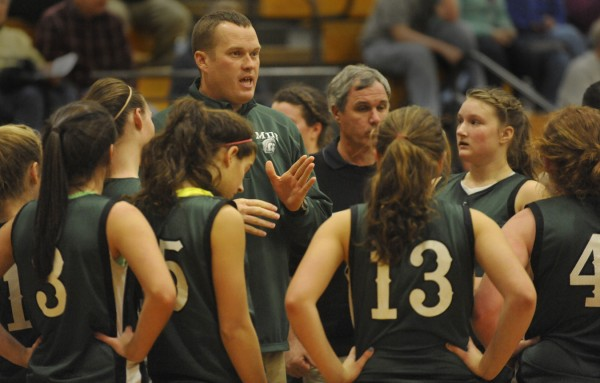 Mount Desert Island varsity coach Brent Barker and other coaching staff huddle with the team before the start of the third quarter of their basketball game at Hermon High School last season. Barker will be competing in the Maine Amateur Golf Championship on Tuesday at Sunday River Golf Club in Newry.